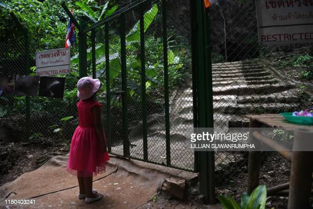 """This picture taken on June 13, 2019 shows a girl looking through a gate at the entrance of the Tham Luang cave, in which 12 boys from the """"Wild..."""