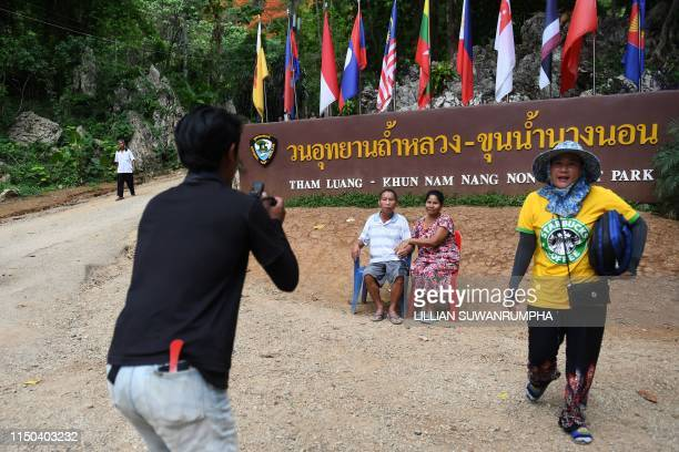"""This picture taken on June 13, 2019 shows visitors posing for photos near the entrance of the Tham Luang cave, in which 12 boys from the """"Wild Boars""""..."""