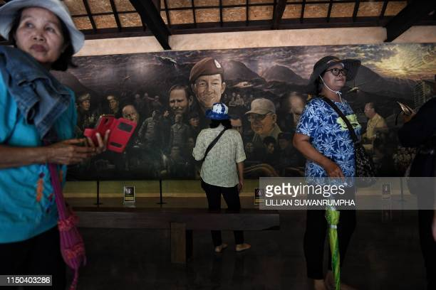 This picture taken on June 13, 2019 shows visitors taking photos in front of a mural, illustrating the efforts to rescue of the 12 boys from the...