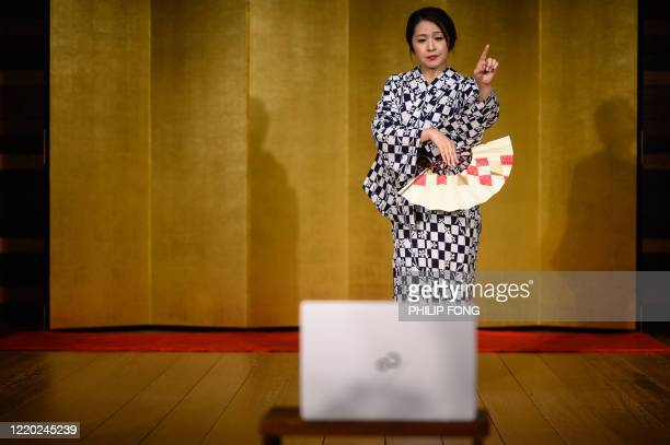 """This picture taken on June 13, 2020 shows geisha """"Chacha"""", who asked to be identified by a pseudonym, dancing during an online drinking party with..."""