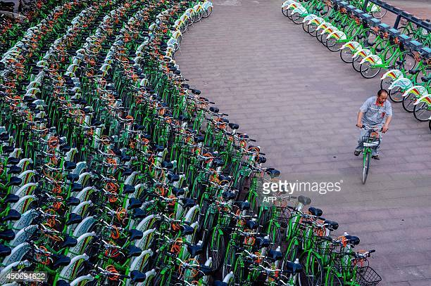 This picture taken on June 14 2014 shows a man rising a public bicycle through a bicyclesharing station in Beijing Beijing is acutely aware of an...