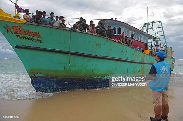 This picture taken on June 14 2016 shows an Indonesian official from the UNHCR speaking to migrants from Sri Lanka stranded along the coast in...