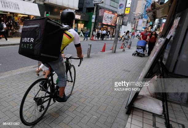 This picture taken on June 14 2018 shows a man delivering an order of food to a customer by bicycle for meal delivery service UberEATS in Tokyo's...