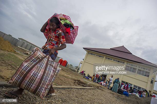 This picture taken on June 15 2015 shows a Myanmar Rohingya man carrying his belongings to new temporary shelters for Rohingyas in Blang Adoe North...