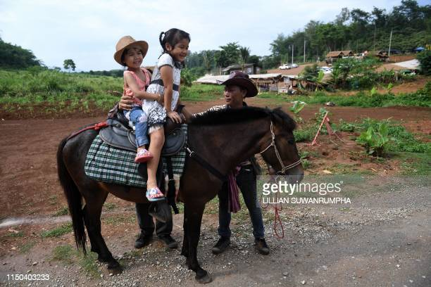 """This picture taken on June 15, 2019 shows girls riding a pony on the road leading to the Tham Luang cave, in which 12 boys from the """"Wild Boars""""..."""