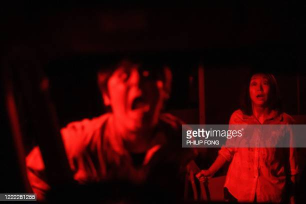 TOPSHOT This picture taken on June 15 2020 shows actors Kenta Iwana and Asami Takeuchi performing during a demonstration of a drivein haunted house...