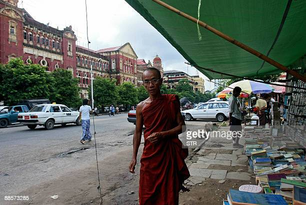 This picture taken on June 16, 2009 shows a Myanmar Buddhist monk walking past the High Court building in Yangon. Myanmar's high court, the Supreme...