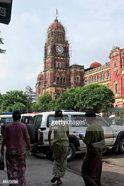 This picture taken on June 16, 2009 shows Myanmar people walking past the High Court building in Yangon. Myanmar's high court, the Supreme Court, was...
