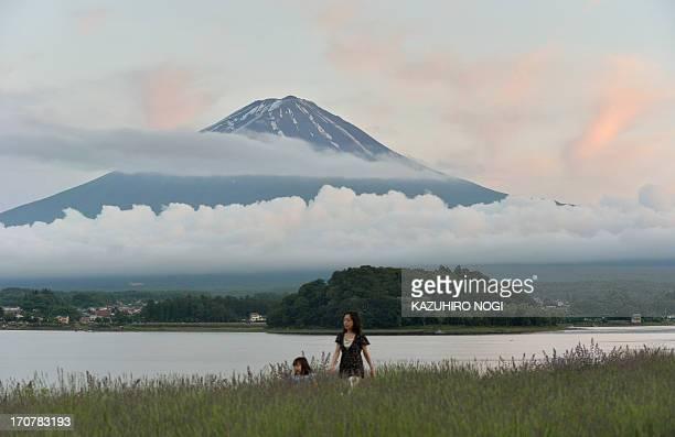 This picture taken on June 16 2013 shows Mount Fuji the highest mountain in Japan at 3776 metres and Lake Kawaguchi in Fujikawaguchiko southern...