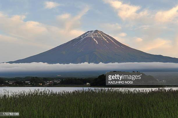 This picture taken on June 16 2013 shows Mount Fuji the highest mountain in Japan at 3776 metres and Lake Kawaguchi in Fujikawaguchiko southern...