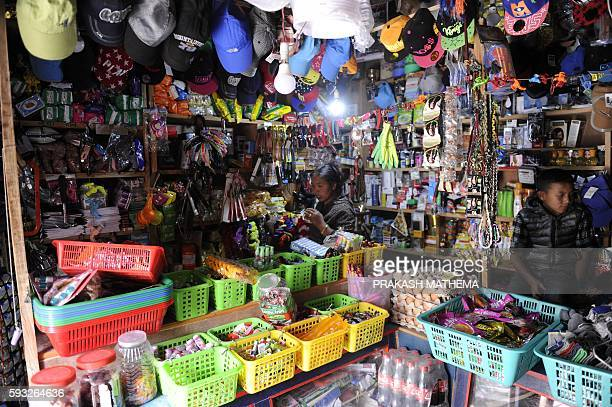 This picture taken on June 16 2016 shows a Nepalese shopkeeper and a young boy surrounded by goods in a shop in Lo Manthang in Upper Mustang A...