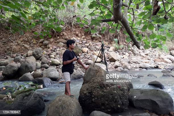 This picture taken on June 16, 2021 shows Indonesian YouTuber Siswanto recording one of his videos next to a water stream in a farming community in...