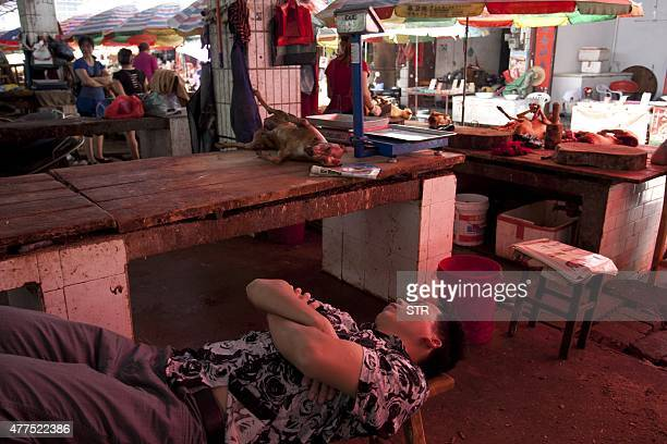 This picture taken on June 17 2015 shows a vendor sleeping by his stall that sells dog meat in Yulin south China's Guangxi province People from Yulin...