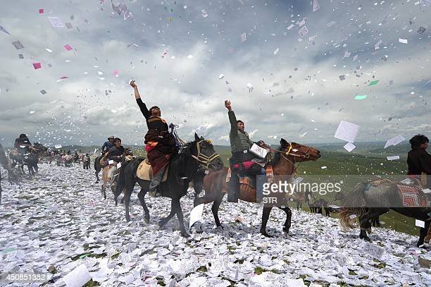 This picture taken on June 18 2014 shows Tibetans throwing 'longda' pieces of prayer paper into the air as they gather to celebrate the wei sang...