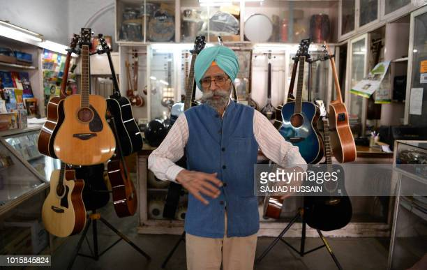 This picture taken on June 19 2018 shows Ajit Singh owner of the music shop who fixed John Lennon's guitar and performed at George Harrison's 25th...