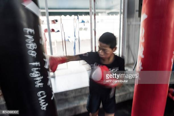 This picture taken on June 2 2017 shows a boy practising boxing during a training session at the Enbo Fight Club in Chengdu Though most of the Enbo...