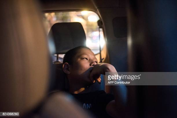This picture taken on June 2 2017 shows a boy resting in a car before fighting in an underground fight club in Chengdu Though most of the Enbo Fight...