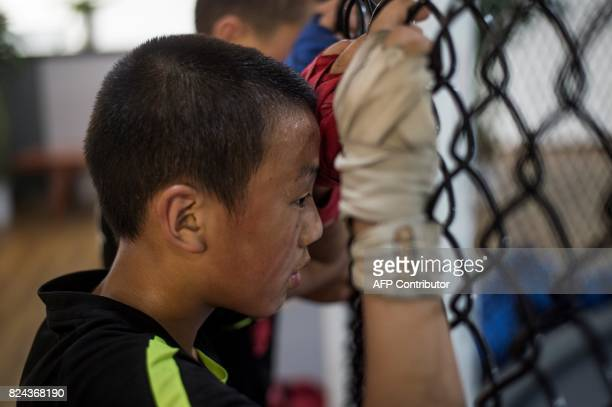 This picture taken on June 2 2017 shows a boy watching a mixed martial arts fight during a training session at the Enbo Fight Club in Chengdu Though...