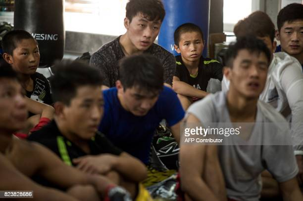 This picture taken on June 2 2017 shows Abieamu listening to a coach about mixed martial arts during a training session at the Enbo Fight Club in...