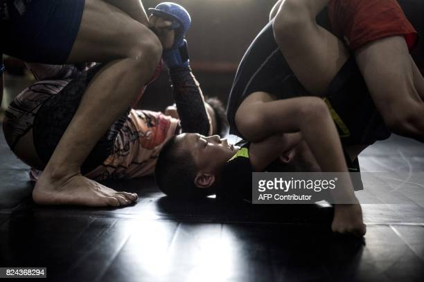 This picture taken on June 2 2017 shows boys fighting during a training session at the Enbo Fight Club in Chengdu Though most of the Enbo Fight...
