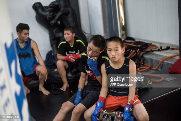 This picture taken on June 2 2017 shows youth waiting to practise during a training session at the Enbo Fight Club in Chengdu Though most of the Enbo...