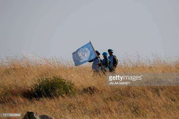 This picture taken on June 2 near the northern Israeli kibbutz of Misgav Am, shows UNIFIL soldiers watching, from the Lebanese village of Adaisseh,...