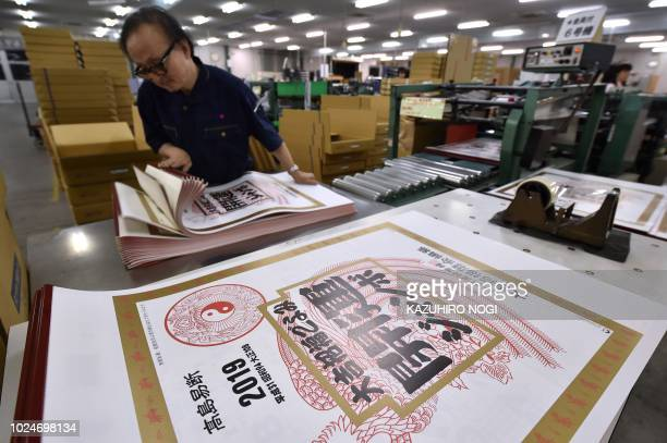 This picture taken on June 20 2018 shows a worker checking the completed 2019 calendar at a factory of Japan's major calender maker Todan in Ami Town...
