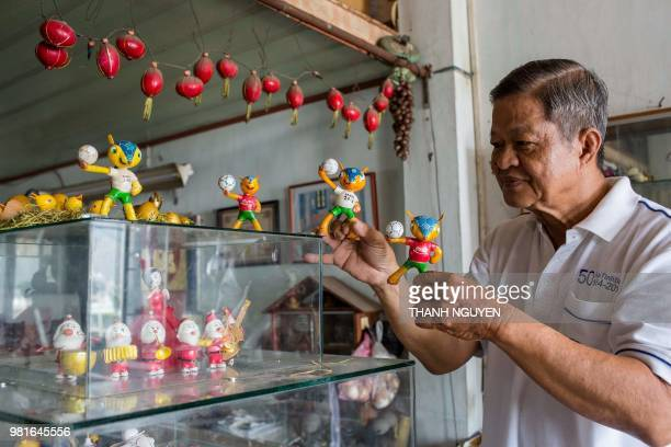 This picture taken on June 20 2018 shows retired Vietnamese English teacher Nguyen Thanh Tam displaying various Football World Cup mascots including...