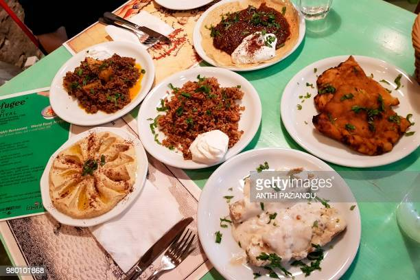 This picture taken on June 20 2018 shows traditional food from Pakistan Syria Afghanistan at the Nan restaurant during refugees food festival in...