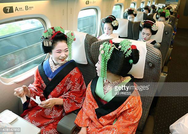This picture taken on June 21 2015 shows apprentice geishas or 'maiko' from Japan's ancient capital Kyoto on a shinkansen bullet train as they move...