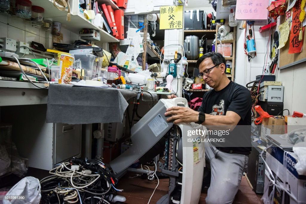 This picture taken on June 21, 2018 shows volunteer electrician Alung Wong repairing a dehumidifier at the headquarters of Fixing Hong Kong, a pro-democracy community group, in the neighbourhood of To Kwa Wan in Hong Kong. - As attendance at Hong Kong's traditional protest rallies wanes, one pro-democracy group is trying to win hearts and minds in a more pragmatic way -- through plumbing, electrics and household repairs. Calling themselves Fixing Hong Kong, the group's volunteers mend broken appliances, furniture, pipes and wiring, hoping that forging community spirit will lead to greater political awareness. (Photo by Isaac LAWRENCE / AFP) / TO GO WITH Hong Kong-politics-lifestyle-social, FEATURE by Elaine YU