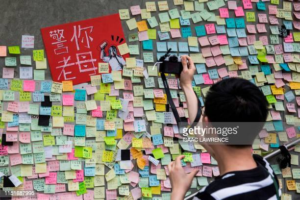 TOPSHOT This picture taken on June 22 2019 shows a man taking photographs of artwork and messages in support of protesters opposed to a China...