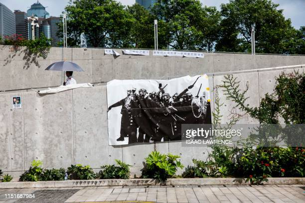 TOPSHOT This picture taken on June 22 shows a security guard walking past a banner depicting riot police during clashes with protesters opposed to a...