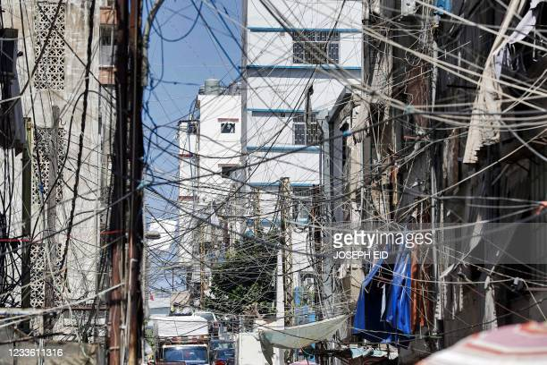 This picture taken on June 23, 2021 shows a view of a mesh of raised electricity lines along a street in a suburb of Lebanon's capital Beirut. - The...