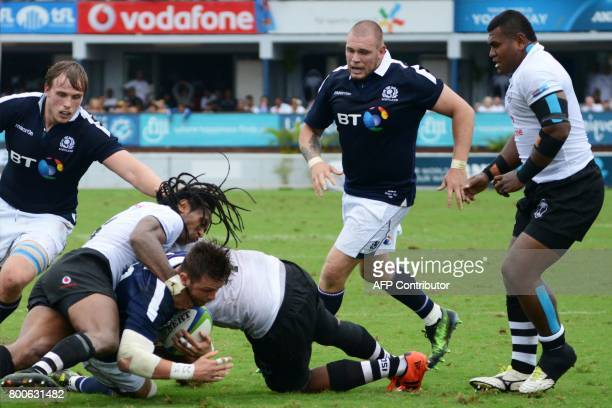 This picture taken on June 24 2017 shows Scotland's Ross Road driving through Fiji's defence for the try line during the oneoff rugby Test match in...