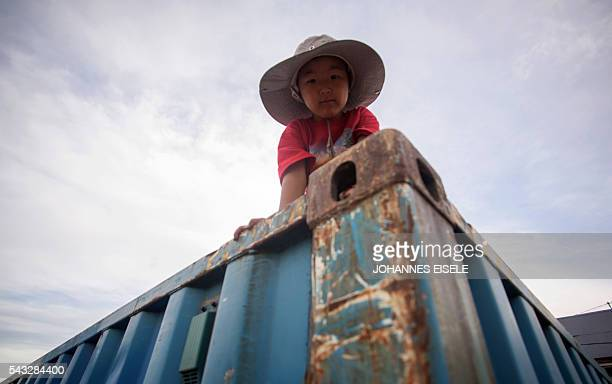 This picture taken on June 25 2016 shows a boy playing in the suburbs of Mongolia's capital Ulan Bator Deep in the Mongolian steppe a gigantic hole...