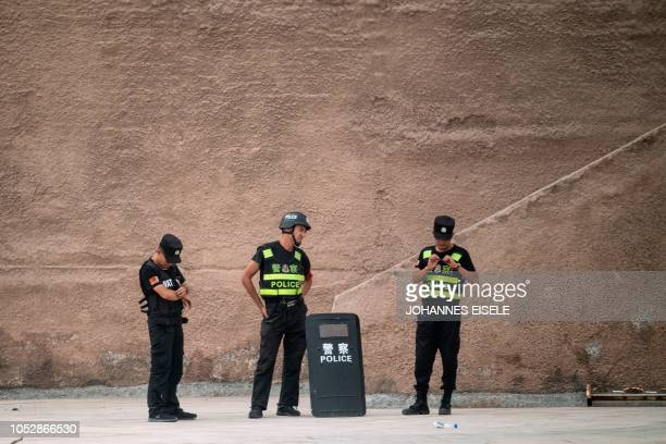 This picture taken on June 25 2017 shows police guarding the streets near the old city in Kashgar in China's Xinjiang Uighur Autonomous Region a day...