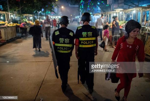 This picture taken on June 25 2017 shows police patrolling in a night food market near the Id Kah Mosque in Kashgar in China's Xinjiang Uighur...