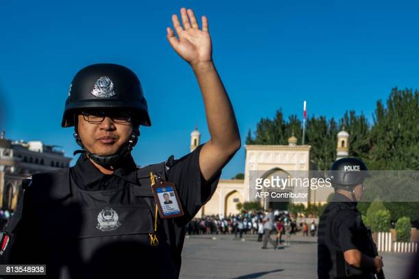 This picture taken on June 26 2017 shows a policeman gesturing as Muslims arrive at the Id Kah Mosque for the morning prayer on Eid alFitr in the old...