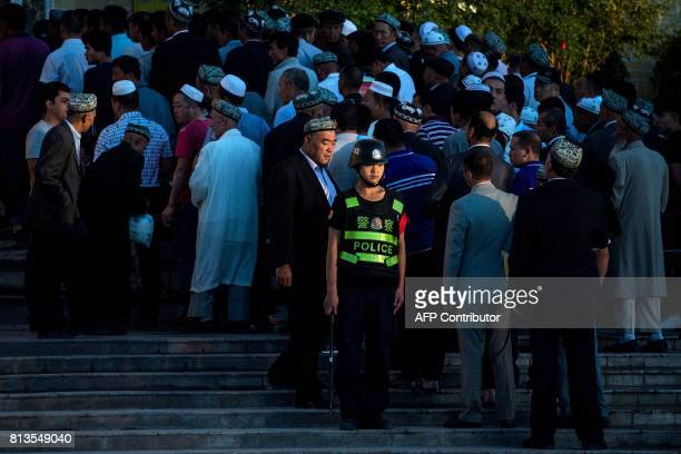 This picture taken on June 26 2017 shows a policeman standing guard as Muslims arrive for the Eid alFitr morning prayer at the Id Kah Mosque in...