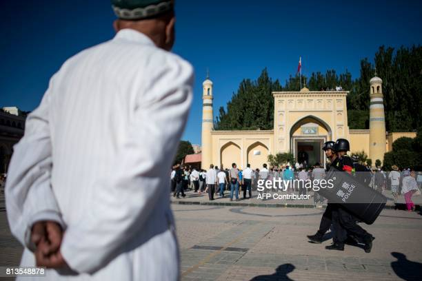 This picture taken on June 26 2017 shows Muslim men arriving at the Id Kah Mosque for the morning prayer on Eid alFitr in the old town of Kashgar in...