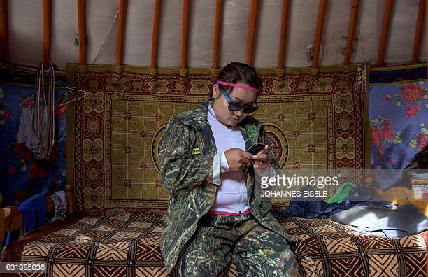This picture taken on June 27 2016 shows national park ranger Surenjav Munkhsaikhan trying to get signal for her mobile phone in a yurt near the...