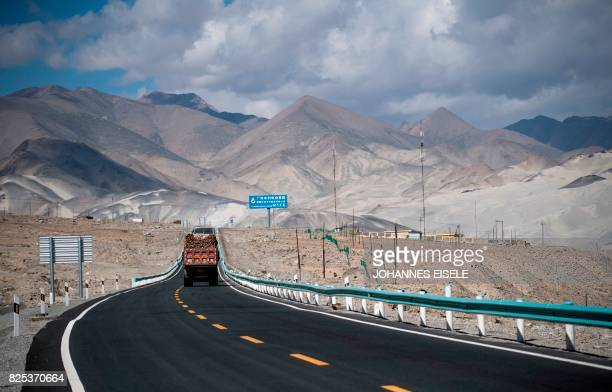 This picture taken on June 27 2017 shows a truck driving along the ChinaPakistan Friendship Highway before the Karakorum mountain range near...