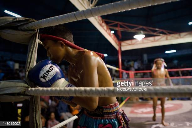 This picture taken on June 28 2012 shows a young Muay Thai boxer paying his respects to the ring at a boxing stadium in Buriram province in the...