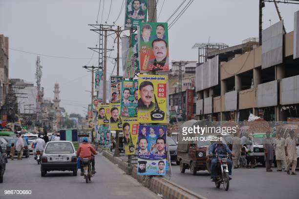 This picture taken on June 28 shows Pakistani motorists driving along a road with posters of candidates taking part in the forthcoming general...
