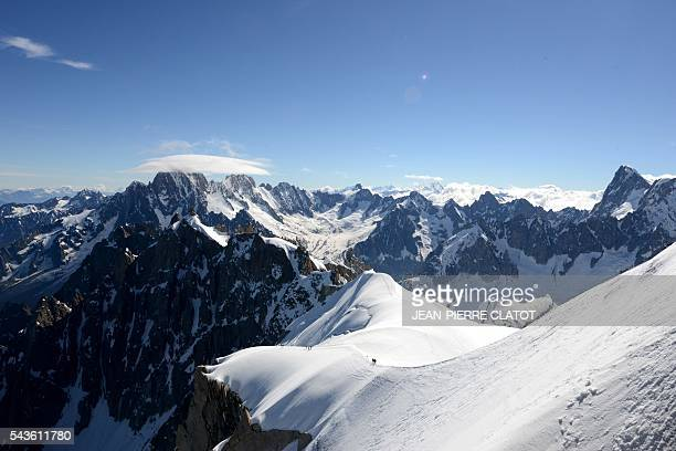 This picture taken on June 29 2016 shows the MontBlanc peak at the top of the Aiguille du Midi mountain above the vallee blanche in the French Alps /...