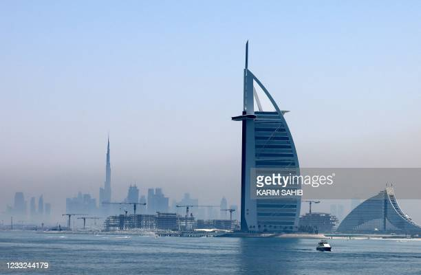 This picture taken on June 3 shows a view of the Burj Al Arab hotel with the Burj Khalifa in the background and the marina of Dubai in the United...