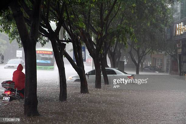 This picture taken on June 30 2013 shows vehicles commuting along a flooded street in Suining southwest China's Sichuan province More than 942000...