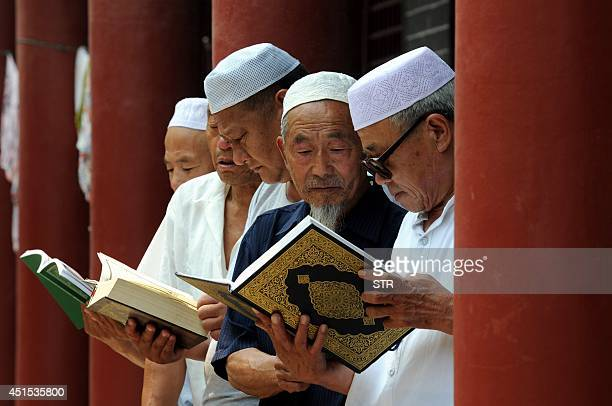 This picture taken on June 30 2014 shows Chinese Muslims reading the Koran at a mosque in Tancheng in eastern China's Shandong province at the...