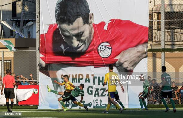 This picture taken on June 30 2019 shows players of Khadamat Rafah Club and Balata Sports Centre vying for the ball during the first leg match of the...